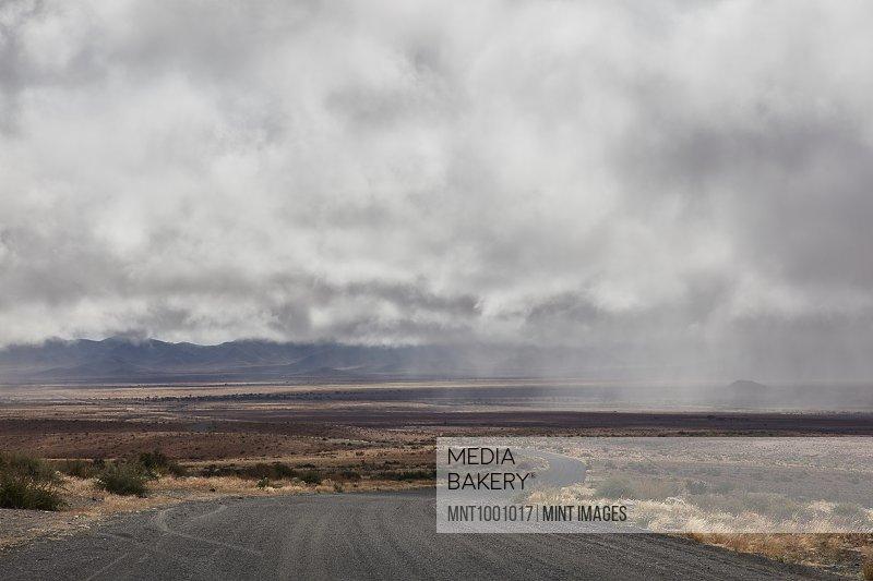 Road running through grassland under storm clouds.