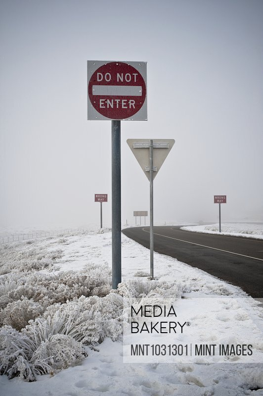 Road signs on road in wintry landscape.