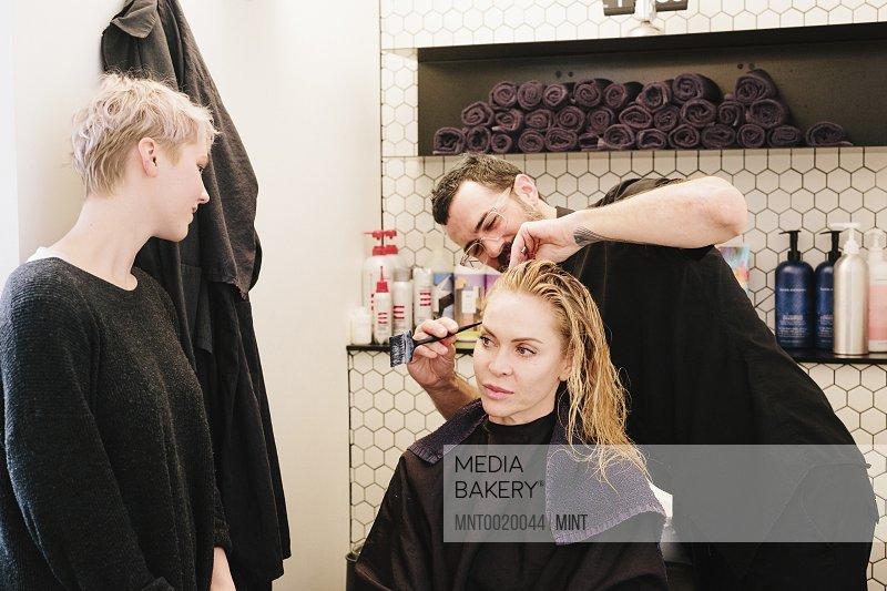 A hair stylist cutting a woman's hair in a hair salon