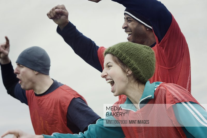 Two men and one woman, friends cheering on their team at a winter sporting event.