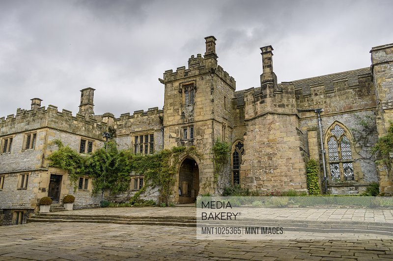 Exterior view of a Tudor fortified house, with a central entrance tower.