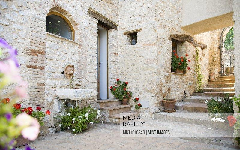 Flowerpots along stone wall in courtyard