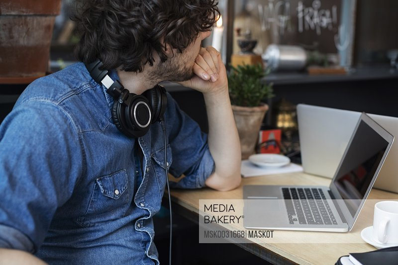 Midsection of man sitting at table with laptop in creative office