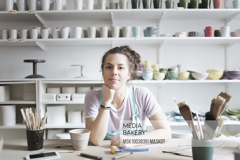 Portrait of confident young female potter sitting at workbench against shelves at store