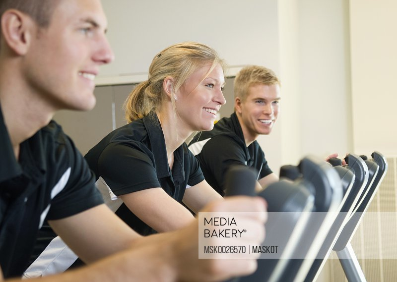Three smiling people working out