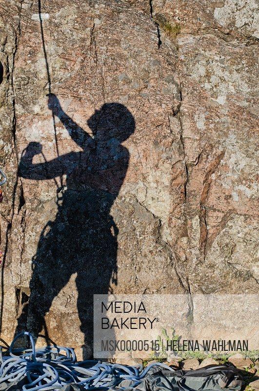 Shadow on rock of woman belaying