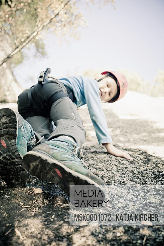 Little boy looking down while doing rock climbing