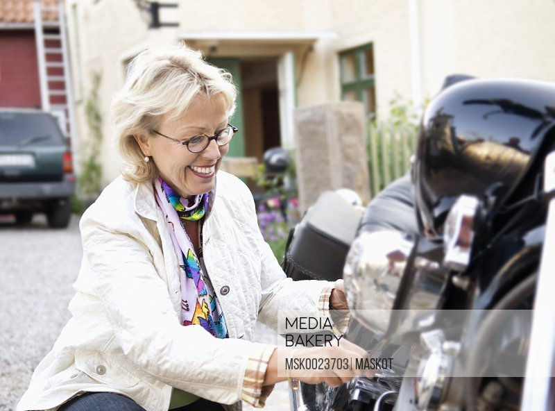 Woman tinker with motorcycle
