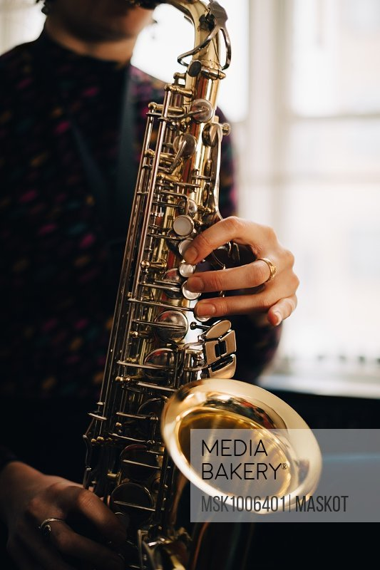 Midsection of woman playing saxophone at studio
