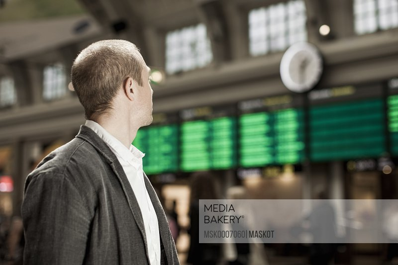 Businessman looking at arrival departure board on railway station