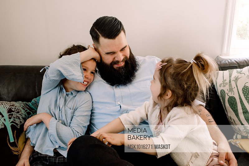 Happy father playing with cheerful daughters while sitting on sofa at home