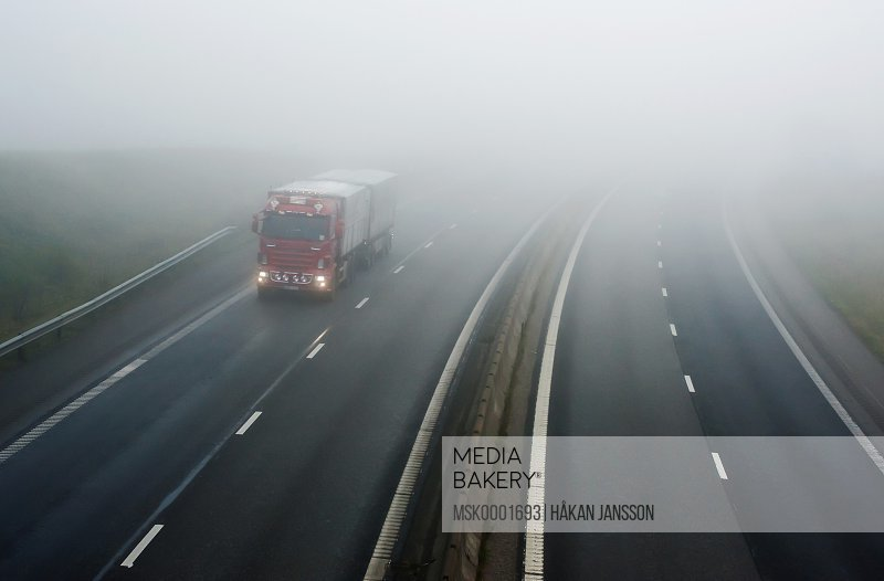 View of four lane highway in low visibility in winter
