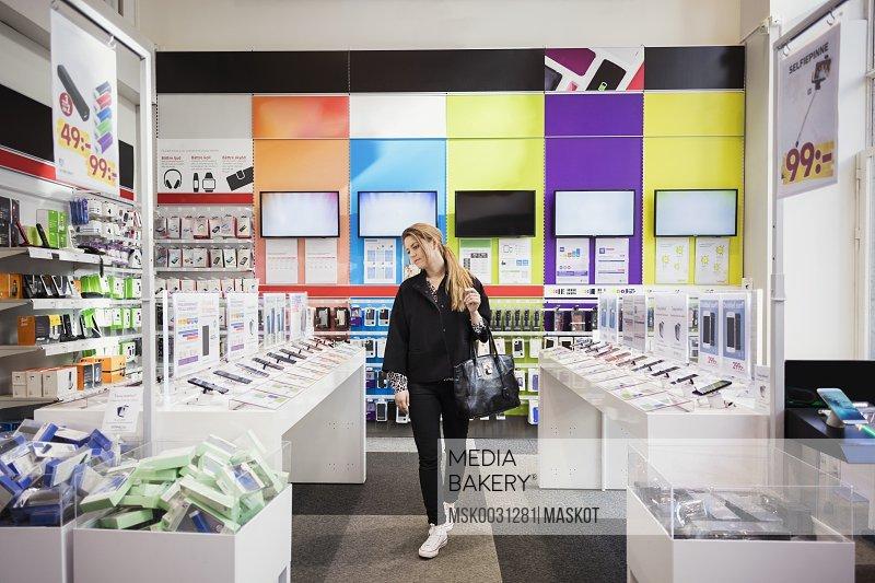 Female customer viewing smart phones in store