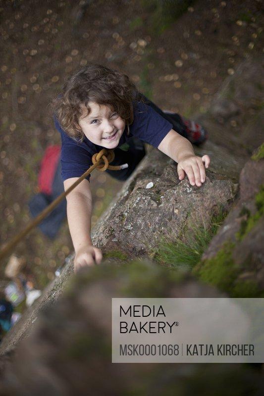 Smiling girl looking at camera while climbing rock