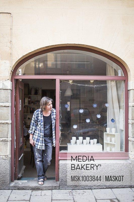 Mature female ceramic store owner standing at doorway while looking away