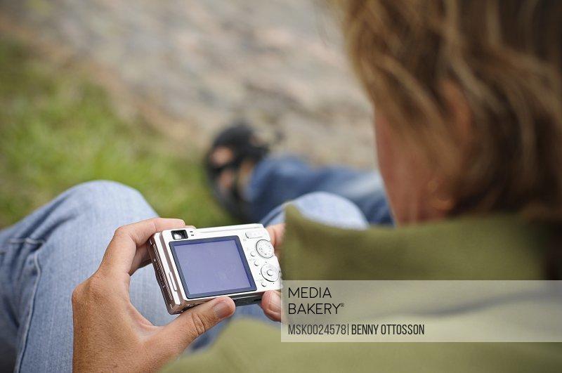 Person looking at digital camera