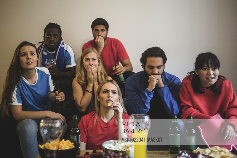 Worried male and female friends watching sport while sitting on sofa at home