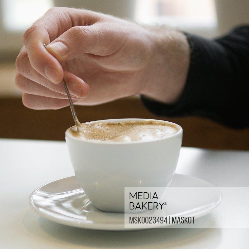 Man stirring in a coffee cup