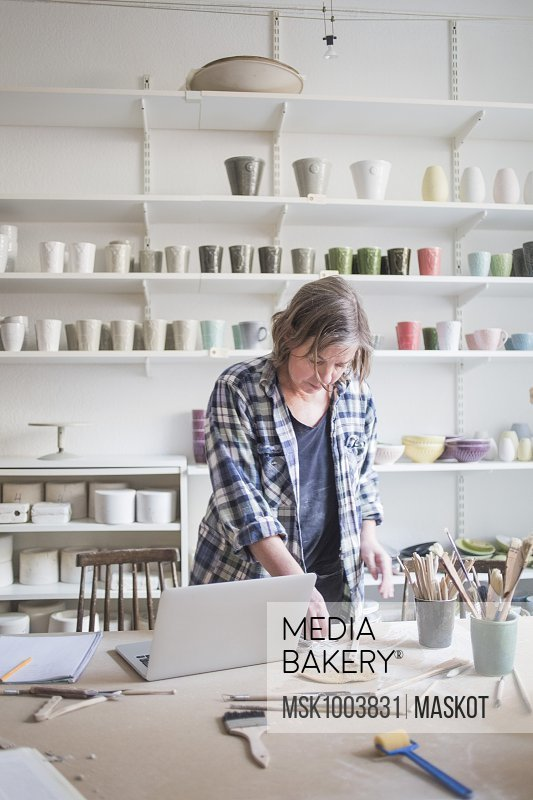 Mature female potter standing with laptop at table in workshop