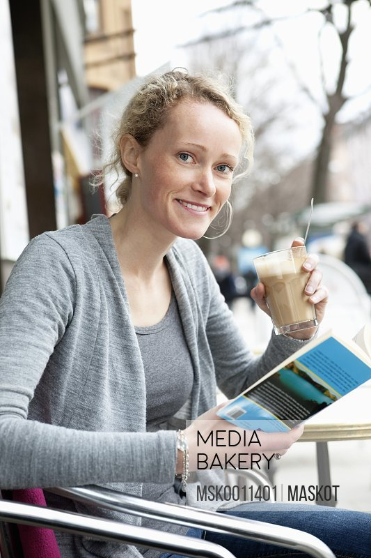 Woman reading book at coffeehouse