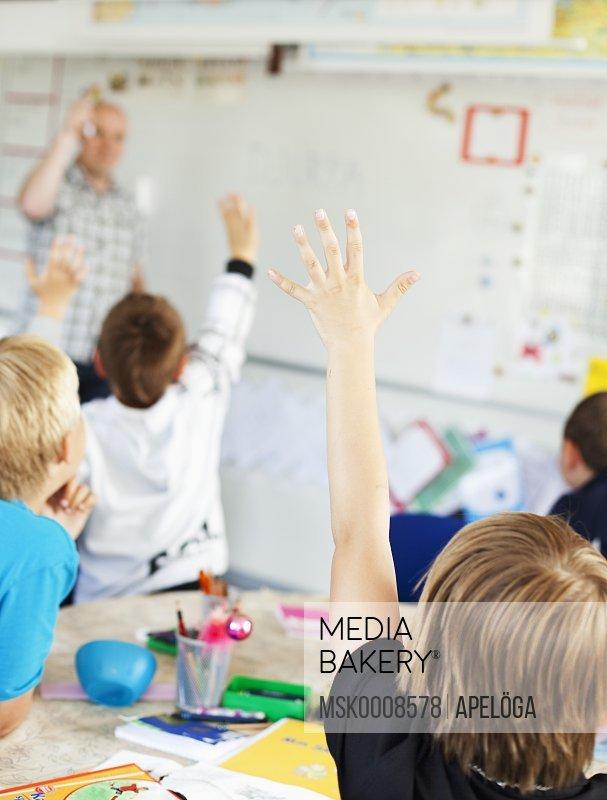 Pupils raising their hands in class