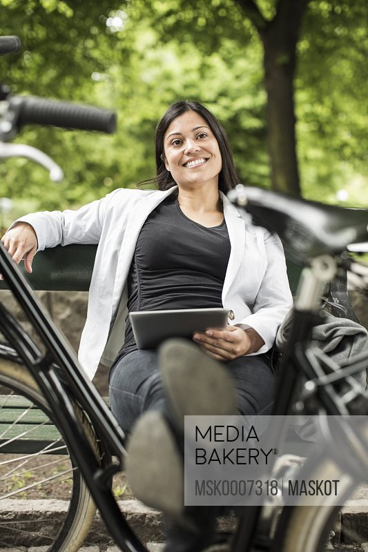 Businesswoman with digital tablet smiling while relaxing on park bench