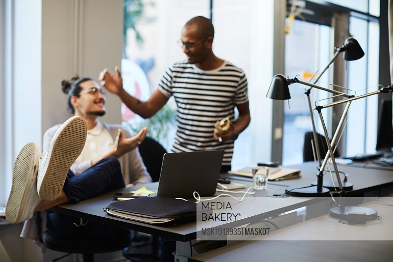 Creative businessmen greeting each other at desk in creative office