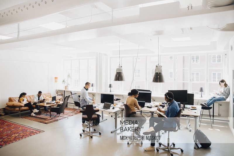 Male and female computer hackers working in creative workplace