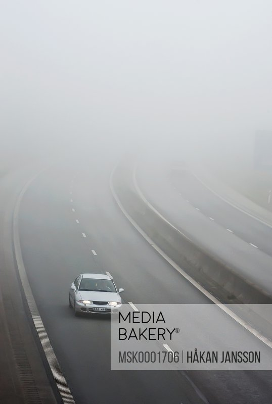 Car moving on four lane highway on foggy road