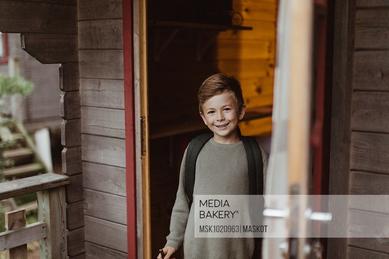 Portrait of smiling boy standing at doorway of house during vacation