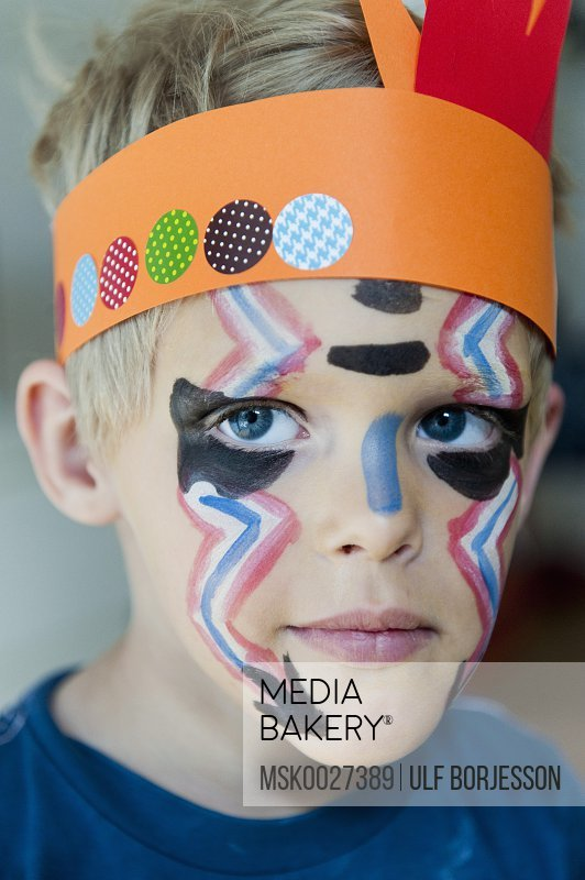 Serious boy 6-7 with painted face
