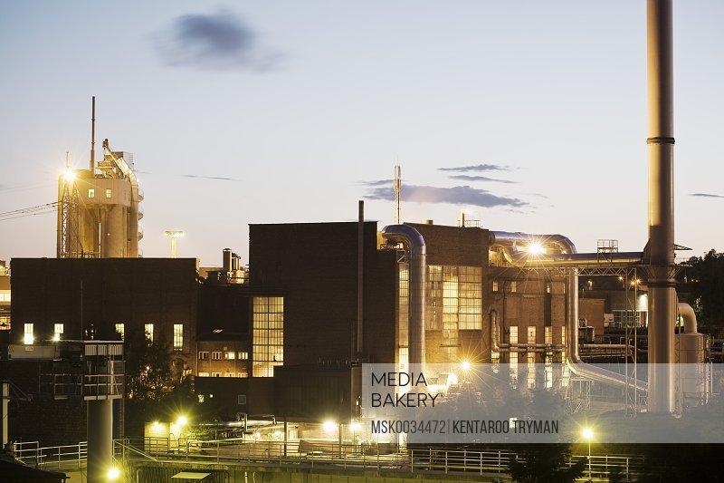 Illuminated factory against sky at twilight