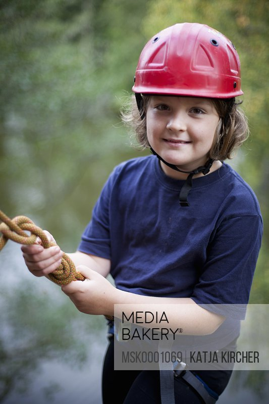 Portrait of happy girl wearing sports helmet for rock climbing