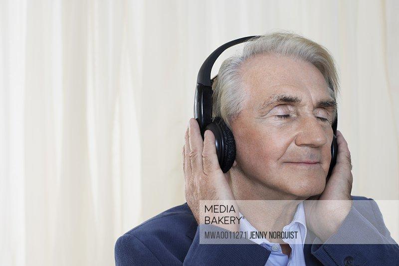 Senior man wearing headphones head and shoulders in studio