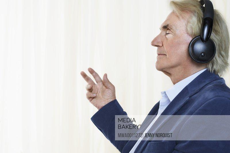 Senior man wearing headphones profile in studio