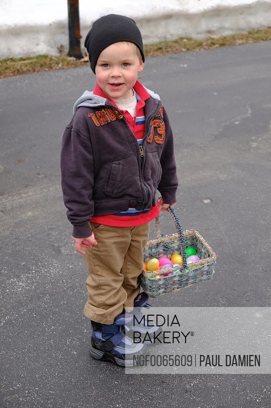 A young boy holds an Easter basket full of colorful eggs at an Easter egg hunt in New Berlin Wisconsin.