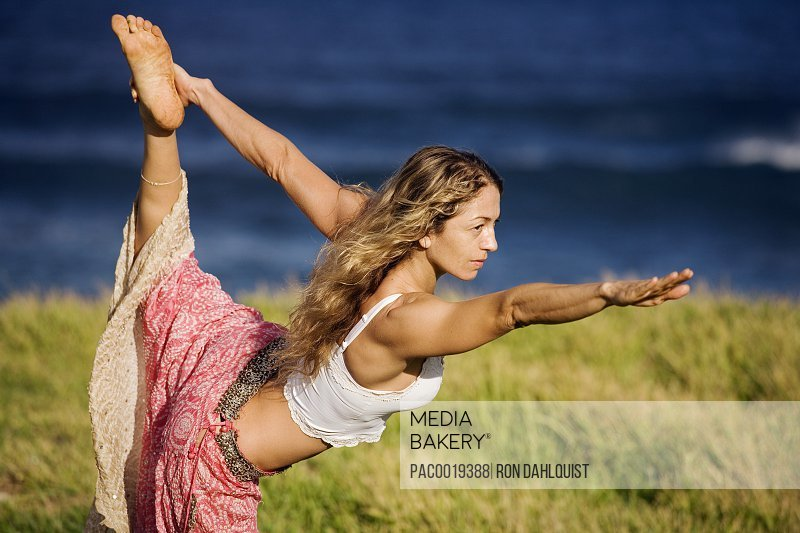 Hawaii, Maui, Young Woman Doing Yoga On Grassy Hill Next To The Ocean.