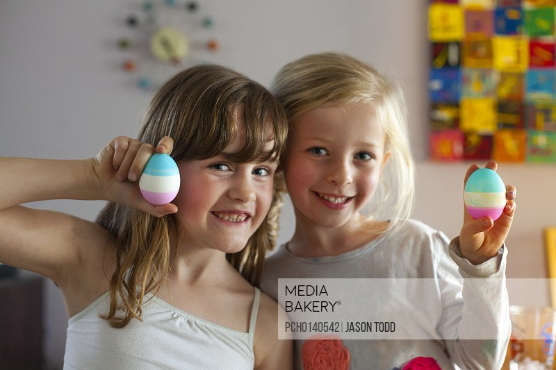 5-7 year old girls holding Easter eggs