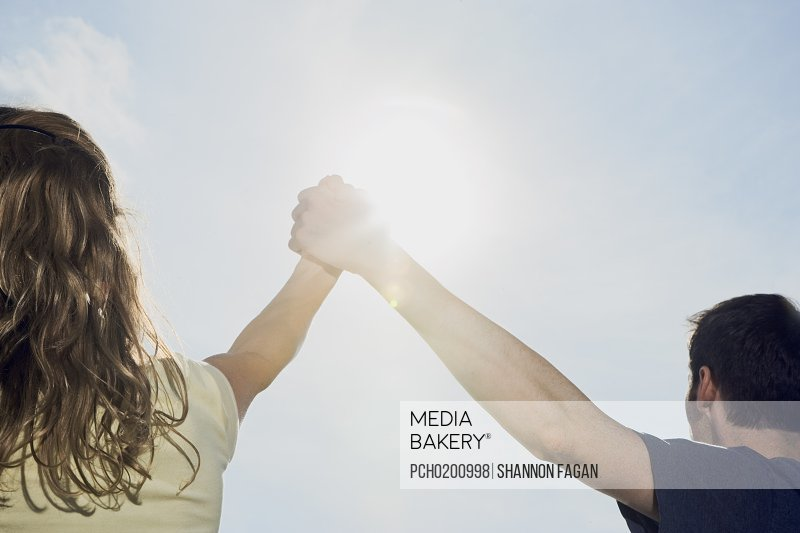 Couple holding hands in excitement with sunlight
