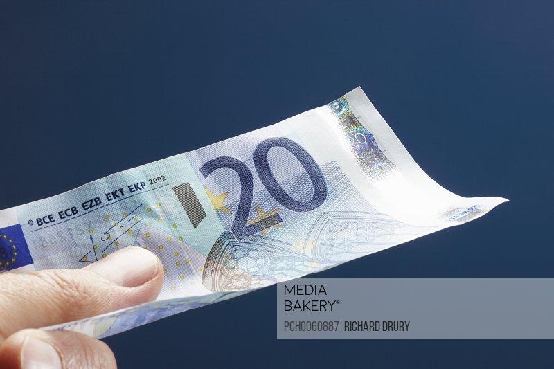 Man holding twenty Euro note