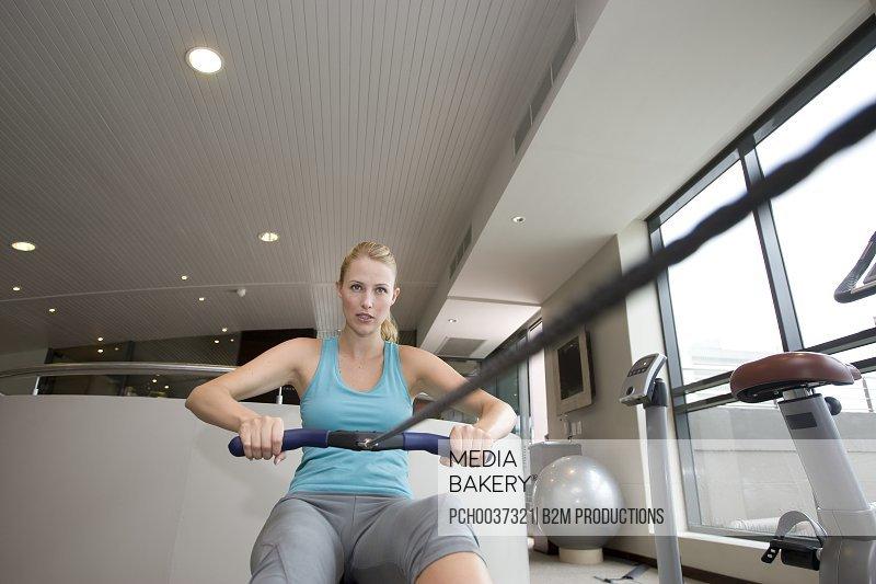 Young woman using rowing machine