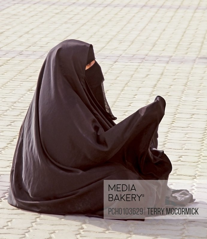 An Arab woman in traditional dress begging