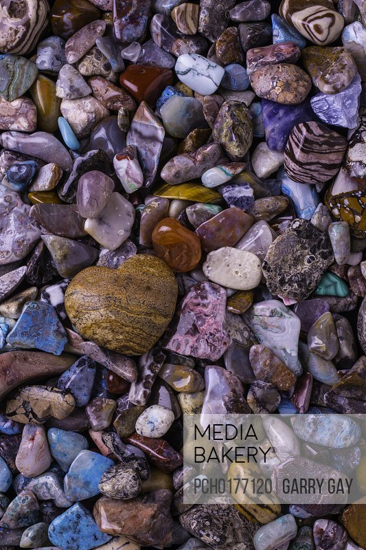 Heart shaped rock among colorful stones love and romance.