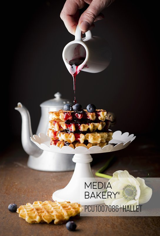 Pouring blueberry coulis onto a pile of waffles Liegeoises