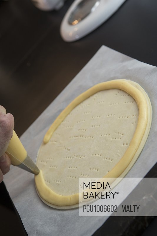 Coating the edges of a flaky pastry disc with choux paste for the preparation of a Saint-Honore