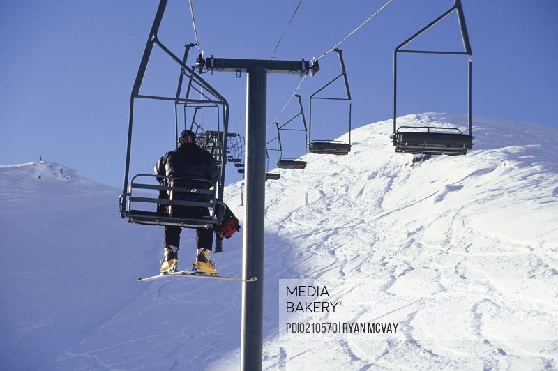 Person going up slope on ski lift