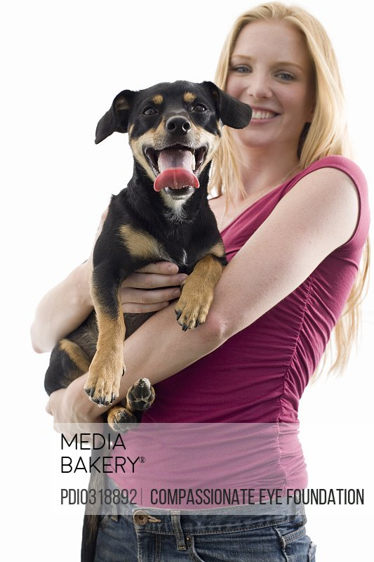 woman holding mixed-breed dog