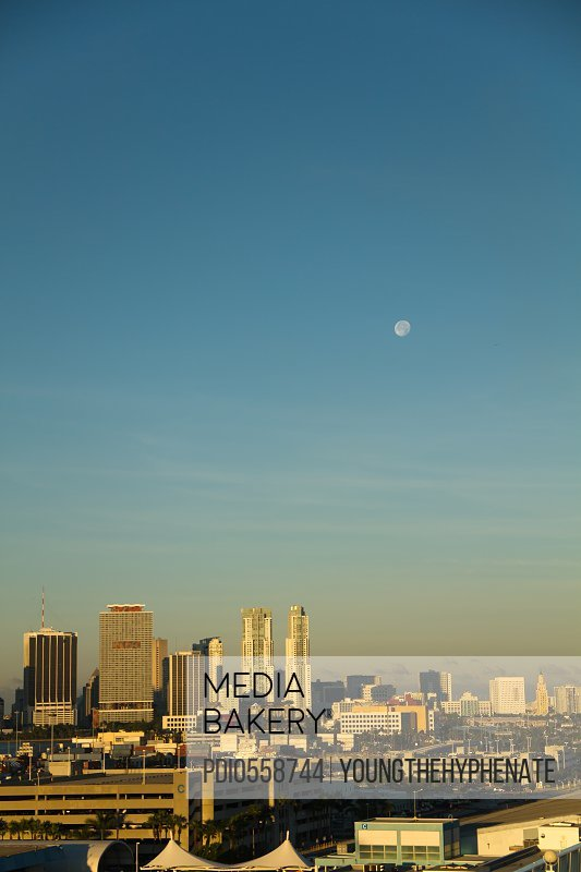 Daytime moon over downtown