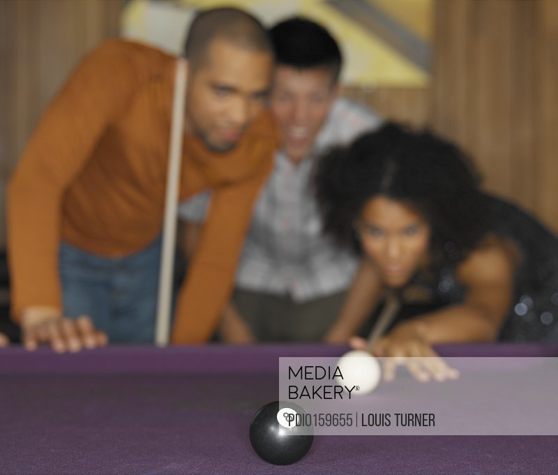 Friends playing pool (focus on '8' ball)
