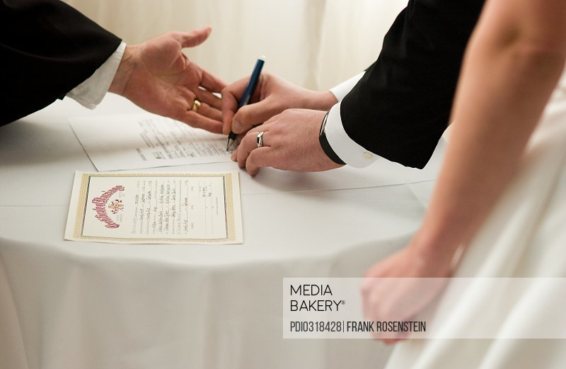 Bride and groom sign their marriage license